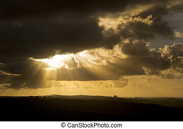 Stunning stormy sky image at sunrise with sun rays