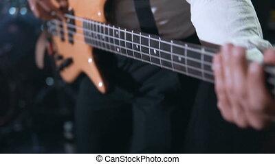 Close Up Bass Guitarist - Guitarist wears white shirt...