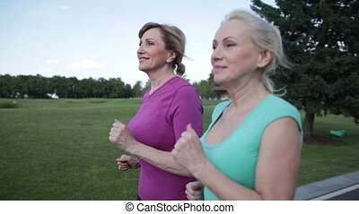 Two pretty senior females joggers training in park - Side...