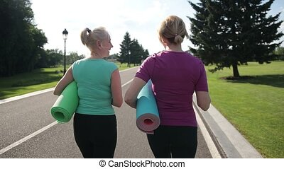 Fitness women with excercise mats going training - Back view...