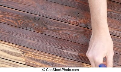 Close-up Paint brush painting wooden table with wood stain