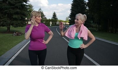 Running females giving high five after training - Cheerful...