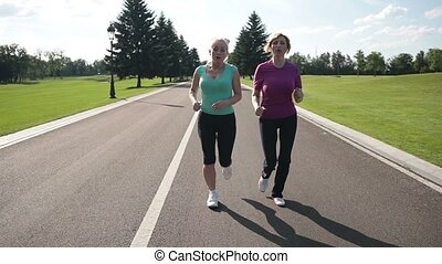Exhausted female runners resting after jogging - Athletic...