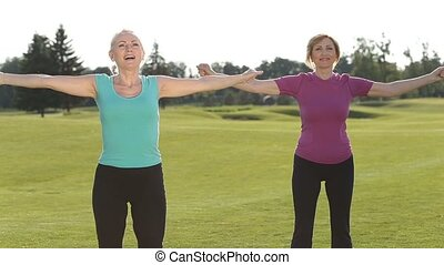 Sporty fitness ladies warm up in park - Beautiful adult fit...
