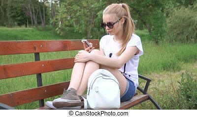 Girl talking on the smart phone sitting in a park on wood bench with green tree leaf, Nature scene