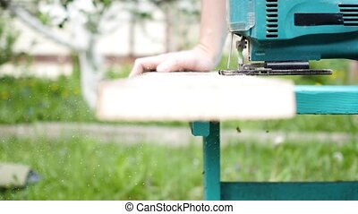 Man saws a board using a jig saw