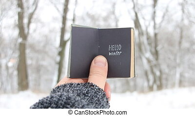 Hello winter. Book with inscription. - Hand holding a book...