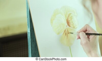 Woman artist on an easel draws a flower beside a butterfly sits 4k