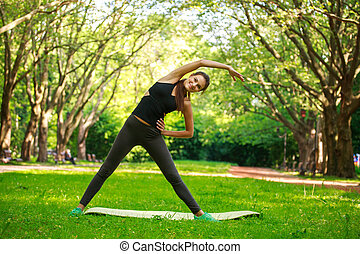 Young woman doing fitness exercises in park