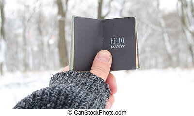 Hello winter. Book with text. - Hand holding a book with the...