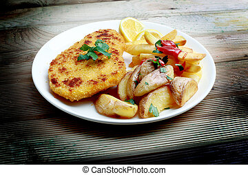 schnitzel and fried potatoes on wood background