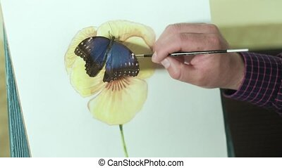Male artist on an easel draws a flower beside a butterfly sits 4k