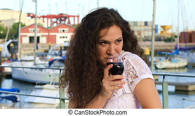 Lovely young woman drinking red wine sitting in a cafe...