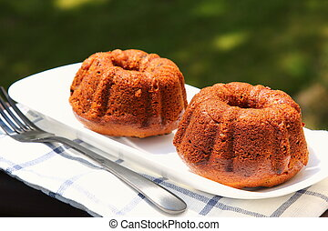 Small banana bread Bundt cakes on a wooden background with...