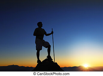 Mountain Top Sunrise - Man at the top of a mountain range at...