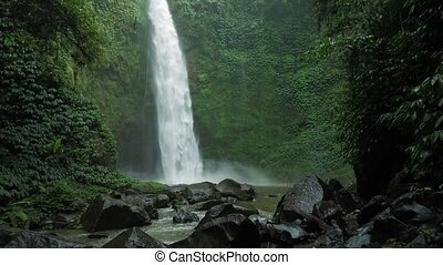 Amazing Nungnung waterfall, slow motioned falling water hitting water surface, some huge rocks seeable in front of frame. Lush green leafes is moving from the wind, Bali, Indonesia