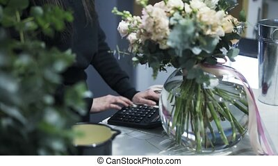 Florist shop owner calculating the cost of a flower bunch