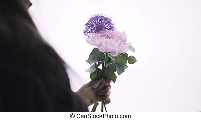 Close up of a woman florist arranging a bunch of purple, white and pink flowers