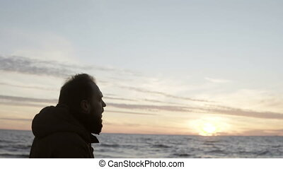 Young man walking in the shore of the sea alone and looking...