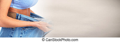 Woman belly fat - Female waist with big jeans over abstract...