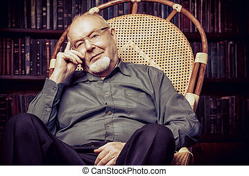 retirement retro style - An old intelligent man reading a...