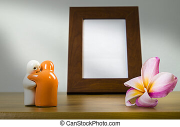 Still life with flowers and white photo frame on wooden...