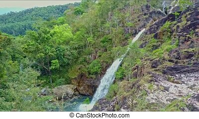 Drone Flies over Hilly Landscape with Waterfall among Forest...