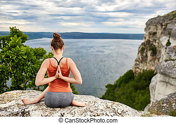 Rear view of young woman in yoga pose sitting on the rock...