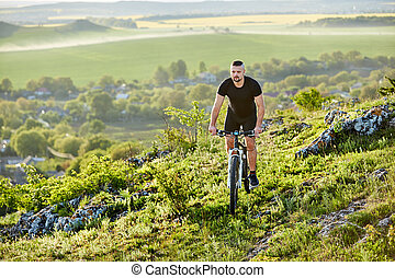 Young cyclist riding the bike on the rocky trail against beautiful landscape.