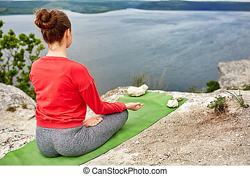 Young woman meditating in a lotus pose on the rock above big...