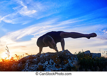 Attractive man doing yoga on the rock in the morning against...