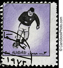 socer player - AJMAN - CIRCA 1960s: A stamp printed in...