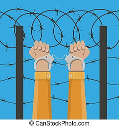 Handcuffs on hands and barbed wire - Human hands in...