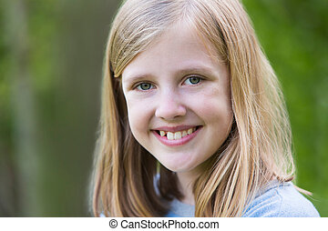 Portrait Of Smiling Pre Teen Girl Outdoors