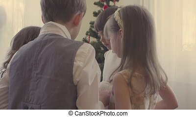 Group of children decorating christmas tree