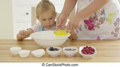 Cute baby helps measure ingredients in kitchen - Single cute...