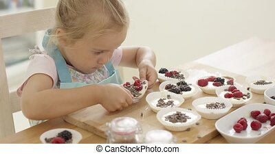 Muffin cups being prepared by little girl - Cute little...