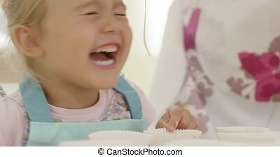 Laughing girl touching empty muffin holders - Close up on...
