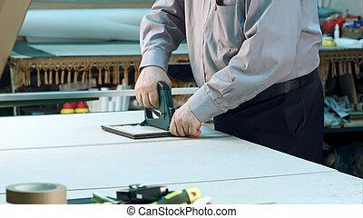 Senior worker finishing frame in workshop. Close up....