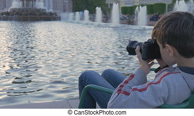 The boy is a teenager, sits in a beautiful spot by the...
