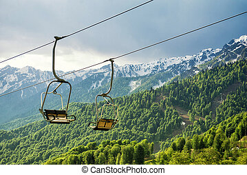 A canopy chairlift in the background of the mountains in the...