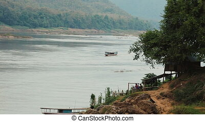 Boat traveling up the Mekong river - Small boat traveling...