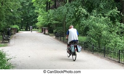 People riding on their bikes in the park - Two people riding...