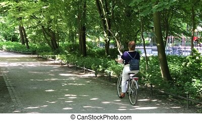sized woman Riding on her bike in the park - sized woman...