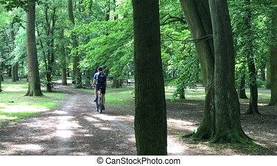 middle aged man riding on his bike In the park