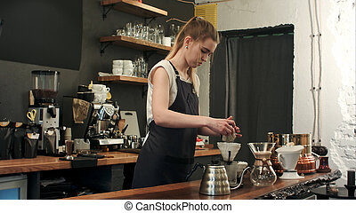 Barista making hand brewed coffee, adding grinded coffee and...