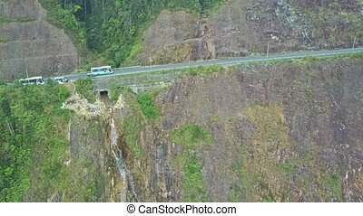 Flycam Shows Bus on Road over Cliff with Beautiful Waterfalls