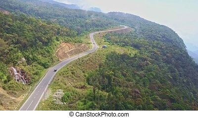 Drone Flies along Modern Mountain Road among Forest - drone...