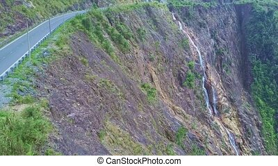 Camera Flies along Highway on Steep Cliff and Waterfall