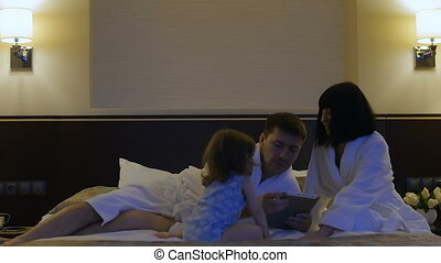 Father with a small child and his wife play with the phone in bed